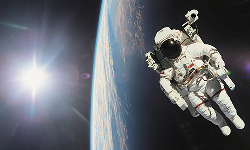 Astronaut in outer space with planet earth as backdrop. Elements